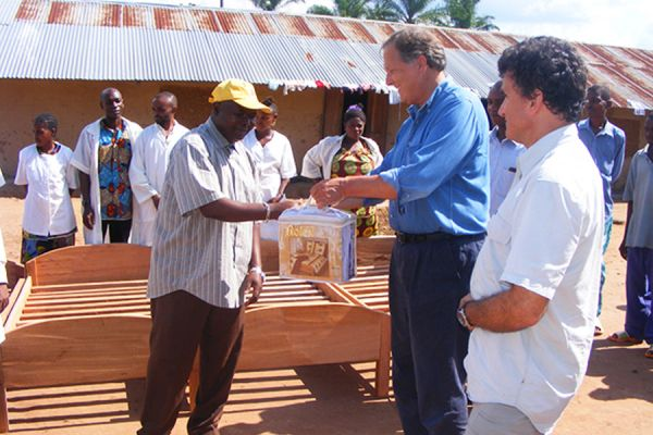 Loncor President Peter Cowley presents the director of the Nia Nia medical clinic near Yindi with a donation of bedding.